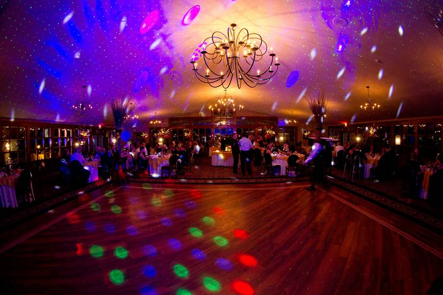Guests seated at tables eating a meal with an empty dance floor, multicolored lights shine around the room