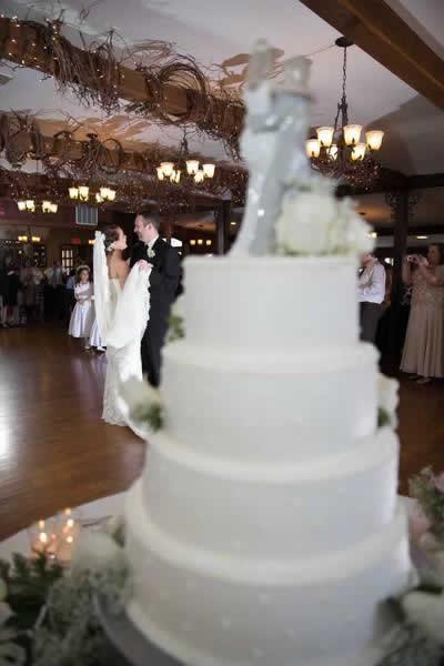 Stroudsmoor Country Inn - Stroudsburg - Poconos - Real Weddings - Wedding Cake With Bride And Groom Dancing In Background