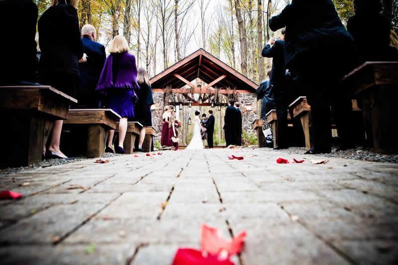 Stroudsmoor Country Inn - Stroudsburg - Poconos - Woodlands Outdoor Wedding - Wedding Couple Under Outdoor Chapel Joined By Wedding Party