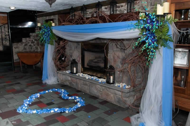Stroudsmoor Country Inn - Stroudsburg - Poconos - Woodlands Outdoor Wedding - Colorful Sash With Flowers Draping Fireplace - Floral Heart On Floor