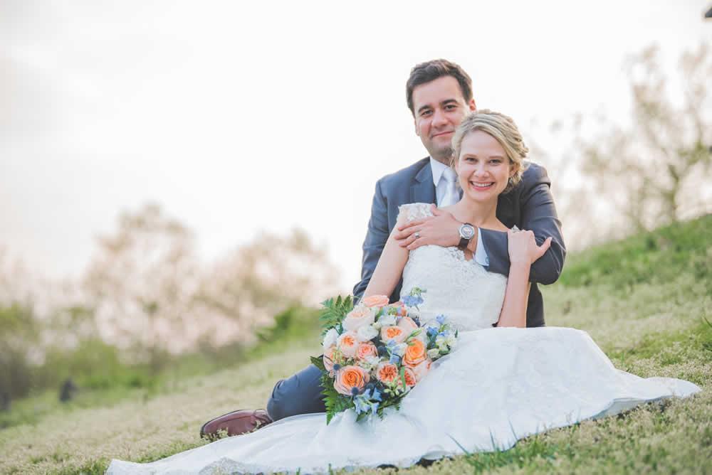 Wedding couple posing, sitting in a field
