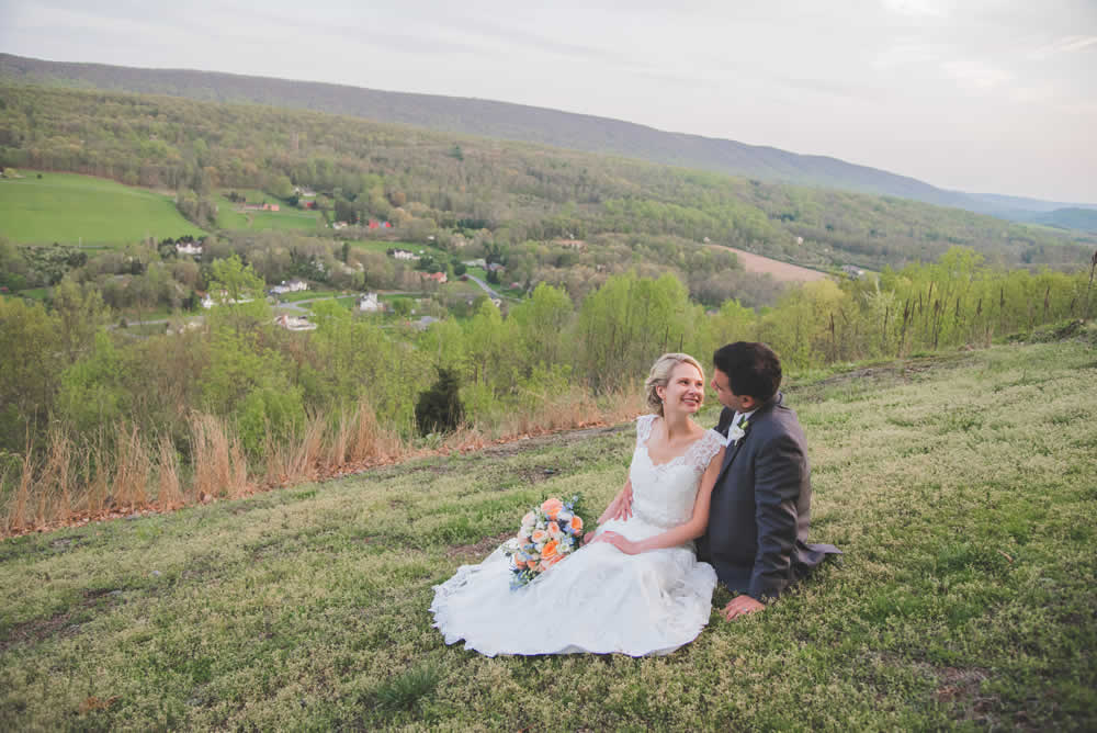 Wedding couple posing, sitting in a field, looking at one another