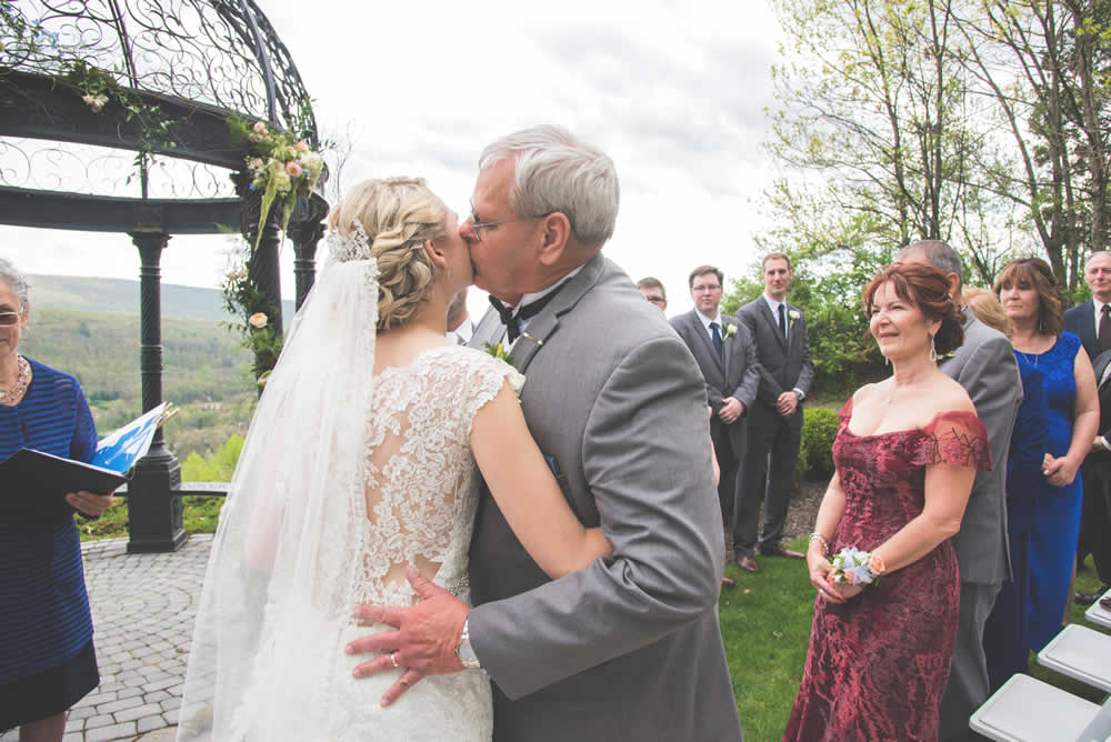 Father kissing bride at wedding ceremony