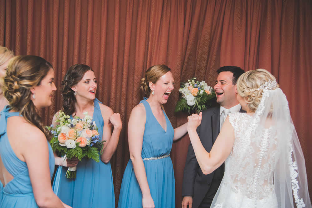 Bride, groom, and bride's maids excited