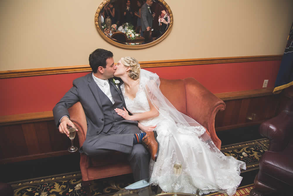 wedding couple kissing on a love seat