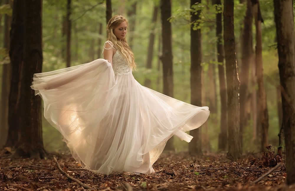 Bride twirling wedding dress in the woods