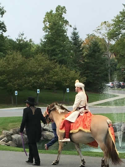 Wedding procession with groom arriving on horseback.