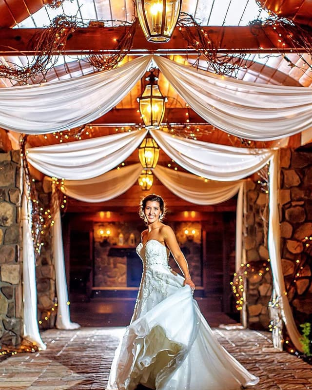 Bride twirling under drapes of sheer fabric and light