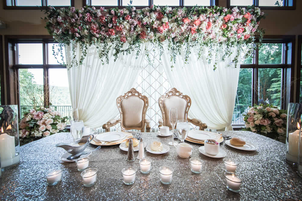 Wedding couple table setting with flowers and draped white fabric