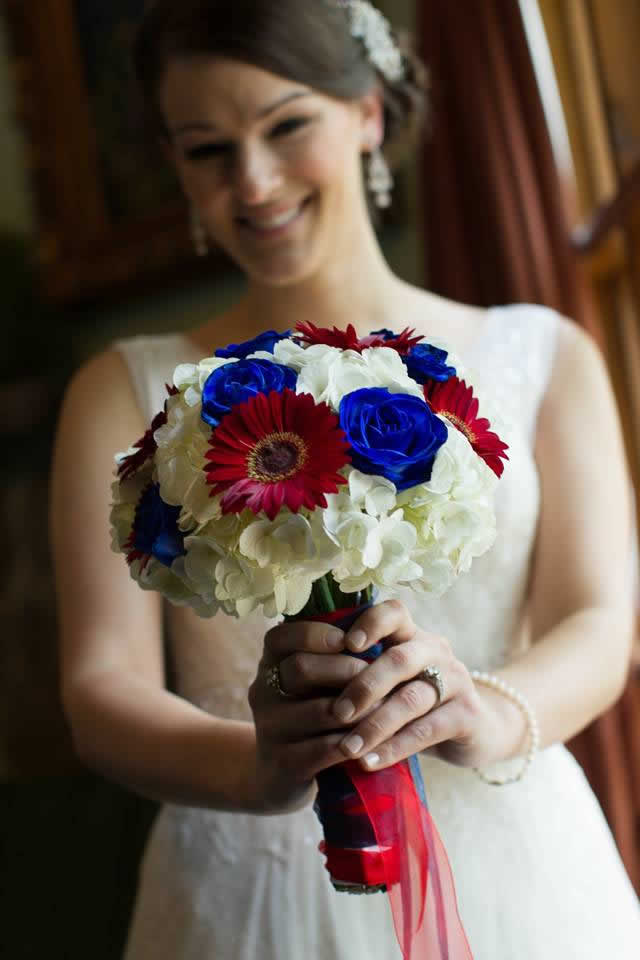 Bride holding red, white, and blue themed flower bouquet