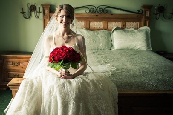 Bride sitting holding a bouquet of roses