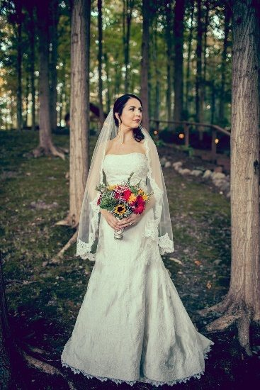 Bride in woods with bouquet of flowers