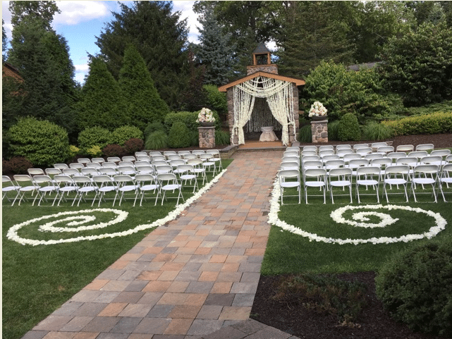 Outdoor altar with white chairs on the lawn with flower petals adorning the grass