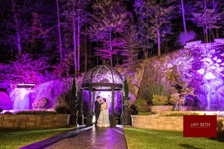 A couple in wedding attire stare at each other in front of an outdoor altar. It is nighttime and they are alone. The rocks and trees behind them are lit in purple lights.