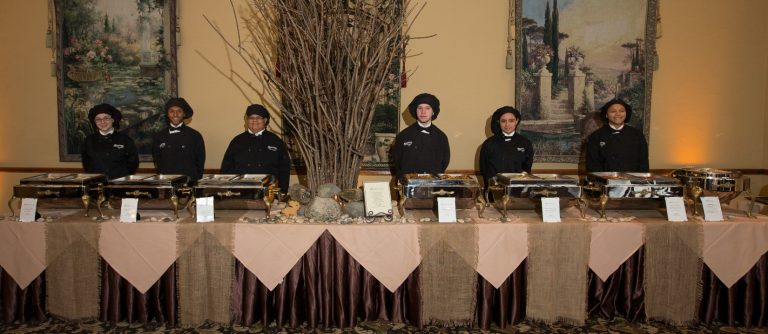 A long table dressed in maroon and tan linens with multiple serving trays of buffet style food. Six servers stand behind the table with black chef uniform and hats.