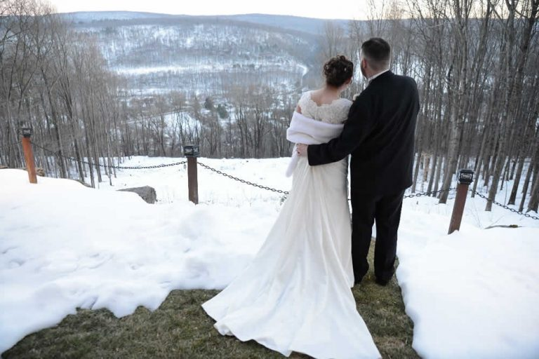 Back of a bride and groom standing at the cliffs looking out over a winter mountain scene
