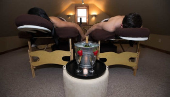 A couple are face down on massage beds while holding hands. A bucket of champagne is in between them.