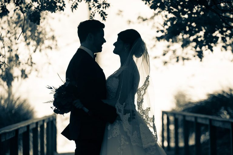 A couple in wedding attire stare at each other under the trees