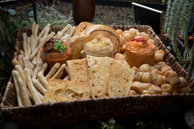 A basket filled with foods including bread sticks and hummus