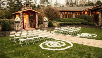 An outdoor wedding ceremony set up with a stone altar and white chairs on the lawn.