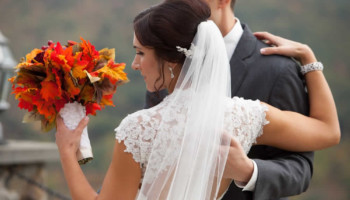 A bride holds a bouquet of autumn colored leaves. Her arms is around her groom.