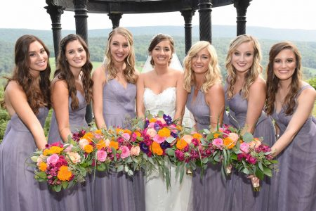 Bride and bridesmaids posing with bouquets at Ridgecrest wedding venue