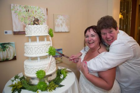 Couple cutting three layered wedding cake LGBTQ